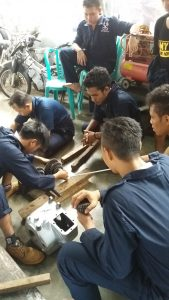 Siswa yang sedang memperbaiki mesin motor di LPK Rotor Rotari