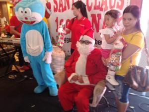 Salah seorang anak bersama ibunya saat pengambilan bingkisan dari santa