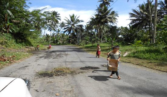 Foto: Anak-anak sedang menimbun jalan yang berlobang sambil meminta uang kepada pengendara yang melintasi jalan tersebut.